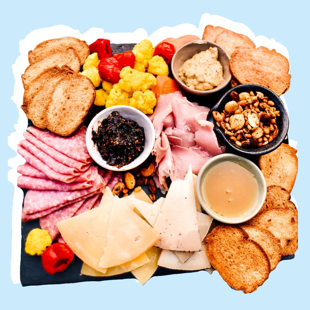 charcuterie board with meats, cheeses, nuts, breads, and sauces